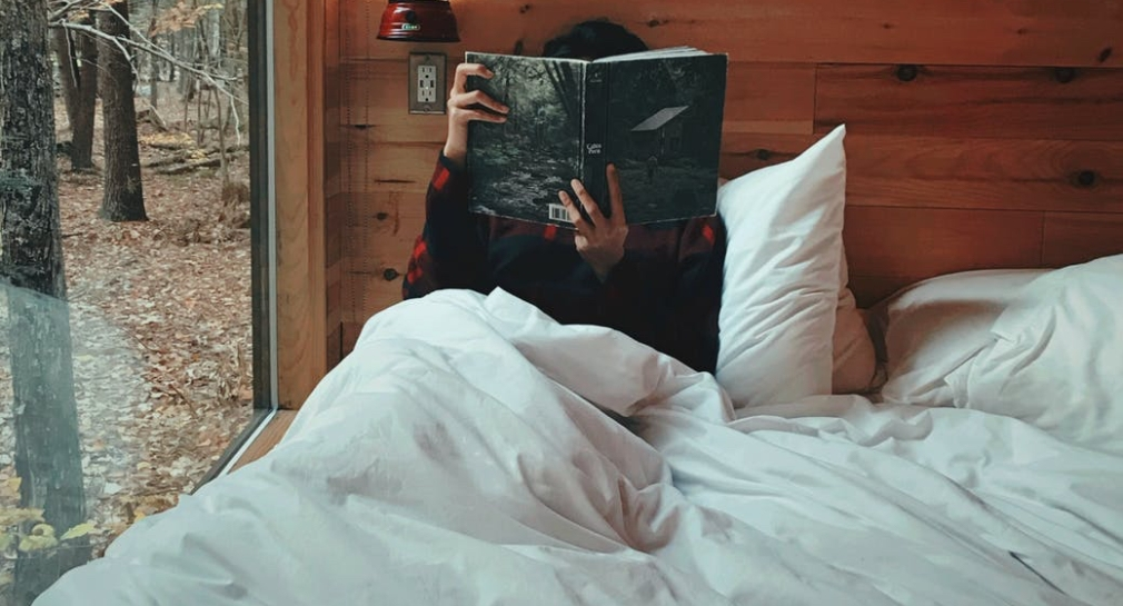 woman sitting in a bed covered in fluffy white pillows and a white duvet. She is holding up a book to read and leaning agains a wood paneled wall. She is in a cabin and looks like she is surrounded by trees in the woods.